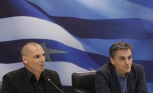 Outgoing Greek Finance Minister Yanis Varoufakis, left, speaks as the new Finance Minister Euclid Tsakalotos listens to him during a hand over ceremony in Athens, Monday, July 6, 2015. Following Sunday's referendum the Greece and its membership in Europe's joint currency faced an uncertain future Monday, with the country under pressure to restart bailout talks with creditors as soon as possible after Greeks resoundingly rejected the notion of more austerity in exchange for aid. (ANSA/AP Photo/Petr David Josek)