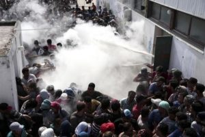 Policemen try to disperse hundreds of migrants by spraying them with fire extinguishers, during a registration procedure which was taking place at the stadium of Kos town, on the southeastern island of Kos, Greece, Tuesday, Aug. 11, 2015. Fights broke out among migrants on the Greek island of Kos Tuesday, where overwhelmed authorities are struggling to contain increasing numbers of people arriving clandestinely on rubber dinghies from the nearby Turkish shore.  (ANSA/AP Photo/Yorgos Karahalis)