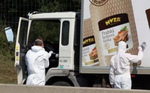 Investigators search  traces at  a  truck that  stands on the shoulder of the highway A4 near Parndorf south of Vienna, Austria, Thursday, Aug 27, 2015. At least 20 migrants were found dead in the truck parked on the Austrian highway leading from the Hungarian border, police said. (ANSA/AP Photo/Ronald Zak)