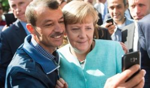 epaselect epa04923489 German Chancellor Angela Merkel (R) has a selfie taken with a refugee during a visit to a refugee reception centre in Berlin, Germany, 10 September 2015. Germany can deal with the arrival of hundreds of thousands of refugees without cutting social welfare benefits or raise taxes, Vice Chancellor Sigmar Gabriel said on 10 September, during a debate in parliament on next year's budget. Germany expects 800,000 asylum seekers this year, four times more than last year and more than any other country in the European Union, which is split on how to deal with the biggest refugee crisis since World War II. EPA/BERND VON JUTRCZENKA