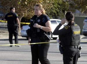epa05052385 Law enforcement officers guard the road leading towards the scene of a shooting at the Inland Regional Center in San Bernardino, California, USA, 02 December 2015. A shooting at a government building west of Los Angeles left 'upwards of 14 people' dead and at least 14 wounded, San Bernardino Police Chief Jerrod Burguan says. EPA/MIKE NELSON