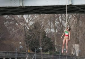 A Femen activist, Sarah Constantin, is hanged from a noose-like rope from a Paris bridge to call attention to the large number of executions in Iran as she stages a protest against visiting Iranian President Hassan Rouhani in Paris, Thursday, Jan. 28, 2016. A near-naked woman hanging from a noose-like rope from a Paris bridge has sent a message to visiting Iranian President Hassan Rouhani. (ANSA/AP Photo/Zacharie Scheurer)