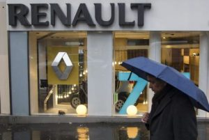 epa05101411 (FILES) A file photo dated 14 December 2012 showing a pedestrian with an umbrella in front of a Renault dealership in Paris, France. According to media reports on 14 January 2016, shares of French carmaker Renault have plunged after investigators apparently searched offices in connection with an emissions probe.  EPA/IAN LANGSDON
