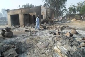 A man walks past burnt out houses following an attack by Boko Haram in Dalori village 5 kilometers (3 miles) from Maiduguri, Nigeria, Sunday Jan. 31, 2016. A survivor hidden in a tree says he watched Boko Haram extremists firebomb huts and listened to the screams of children among people burned to death in the latest attack by Nigeria s homegrown Islamic extremists. (ANSA/AP Photo/Jossy Ola)
