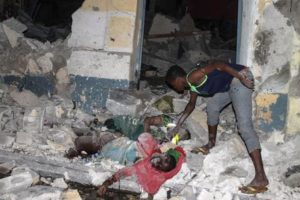 epa05182534 A man inspects bodies in the rubble at the scene of an attack in front of the SYL hotel in Mogadishu, Somalia, 26 February 2016. Gunmen from Somalia's Islamist militant group al-Shabab allegedly detonated a car bomb at the entrance of the hotel and stormed the building, according to reports. A witness said at least 10 bodies were seen on the ground. The latest attack by al-Shabab comes a day after another attack in the city claimed by al-Shabab. EPA/SAID YUSUF WARSAME PICTURE CONTAINS GRAPHIC CONTENT