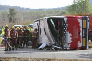 epa05222061 Firemen work at the site of a coach crash that has left at least 14 students dead at the AP-7 motorway in Freginals, in the province of Tarragona, northeastern Spain, 20 March 2016. The coach carrying dozens of Erasmus students collided with a car and overturned. The students from several different countries were heading to Barcelona after attending Las Fallas Festival in Valencia, eastern Spain. EPA/JAUME SELLART