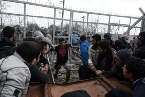 Refugees and migrants try to broke an iron fence from the Greek side of the border as Macedonian police stand guard, near the northern Greek village of Idomeni on Monday, Feb. 29, 2016. No arrests or injuries were reported. About 6,500 migrants are stuck on the Greek-Macedonian border at Idomeni, waiting to travel north, but Macedonia is only admitting a trickle. (ANSA/AP Photo/Giannis Papanikos)