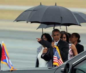 epa05223329 US President Barack Obama (3-R) carries an umbrella as he is followed by First Lady Michelle Obama (2-R) after their arrival on Jose Marti Airport in Havana, Cuba, 20 March 2016. Others are not identified. Barack Obama arrives in Cuba for an official visit until 22 March to seal the process of rapprochement with the Communist-ruled island. Obama is accompanied by his wife Michelle, his daughters Malia and Sasha, and his mother-in-law Marian Robinson. The visit of Obama to Cuba from 20 to 22 March 2016 is the first visit of a US president to Cuba since US President Calvin Coolidge's visit 88 years ago. EPA/ALEJANDRO ERNESTO