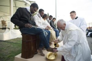 Pope Francis washes the foot of a man during the foot-washing ritual at the Castelnuovo di Porto refugees center, some 30km (18, 6 miles) from Rome, Thursday, March 24, 2016. The pontiff washed and kissed the feet of Muslim, Orthodox, Hindu and Catholic refugees Thursday, declaring them children of the same God, in a gesture of welcome and brotherhood at a time when anti-Muslim and anti-immigrant sentiment has spiked following the Brussels attacks. (L'Osservatore Romano/Pool Photo via AP)