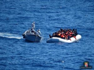 Italian Navy personnel, left, approach a rubber dinghy filled with migrants in the Sicily channel, Mediterranean Sea, Friday, March 18, 2016. The Italian navy rescued Friday 486 migrants in the Sicily channel, while they were trying to cross the Mediterranean sea to reach Italian coasts. Italian officials say good weather is the main factor behind a spike in migrant crossings from Libya, with mostly Italian ships picking up 3,100 migrants over the last three days. (Italian Navy via AP Photo)