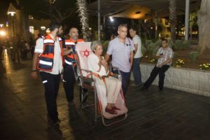 epa05352124 Israeli emergency personnel carrying Israeli woman at the scene of a shooting outside Max Brenner restaurant in Sarona market in Tel Aviv, Israel, 08 June 2016. According to reports, at least three people were killed and five seriously injured in a shooting in Tel Aviv's Sarona complex. EPA/JOHANNA GERON