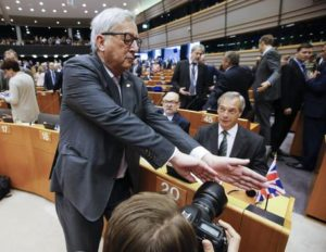 epa05395719 European Commission President Jean- Claude Juncker (L) tries to block a photographer's view on Nigel Farage (R), leader of the United Kingdom Independence Party (UKIP), prior to the start of a plenary session of the European Parliament, in Brussels, Belgium, 28 June 2016. The session will focus on the so-called 'Brexit' and is held ahead of a EU Summit. Later this afternoon EU leaders will met for the first time since the British referendum, in which 51.9 percent voted to leave the European Union (EU).  EPA/OLIVIER HOSLET