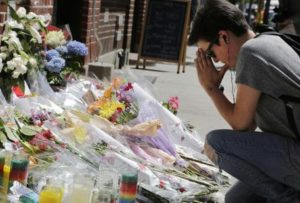 """Zoe Feldman kneels in front of a makeshift memorial in front of New York's Stonewall Inn, Monday, June 13, 2016 to remember the victims of a mass shooting in Orlando, Fla. Morris was college friends with Kimberly Morris, who was working at the nightclub and died in the massacre. """"A lot of my friends knew her and we all are just devastated,"""" said Feldman. A gunman opened fire in a crowded Orlando nightclub early Sunday killing dozens of people. (ANSA/AP Photo/Mark Lennihan) [CopyrightNotice: Copyright 2016 The Associated Press. All rights reserved. This material may not be published, broadcast, rewritten or redistribu]"""