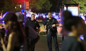 DALLAS, TX - JULY 7: Dallas police and residents stand near the scene where four Dallas police officers were shot and killed on July 7, 2016 in Dallas, Texas. According to reports, shots were fired during a protest being held in downtown Dallas in response to recent fatal shootings of two black men by police - Alton Sterling on July 5, 2016 in Baton Rouge, Louisiana and Philando Castile on July 6, 2016, in Falcon Heights, Minnesota. Ron Jenkins/Getty Images/AFP