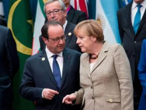 epa04490364 German Chancellor Angela Merkel (R) talks to French President Francois Hollande (L) watch by European Commission President Jean-Claude Juncker (C) as world leaders gather for a family photograph during the G20 summit at the Brisbane Convention and Exhibitions Centre (BCEC) in Brisbane, Australia 15 November 2014. The G20 summit will be held in Brisbane on 15 and 16 November. The G20 represents 90 percent of global gross domestic product, two-thirds of the world's people and four-fifths of international trade. EPA/KAY NIETFELD